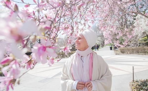 Woman in white byt cherry blossom trees